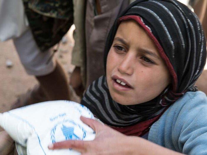 child clutching food bag