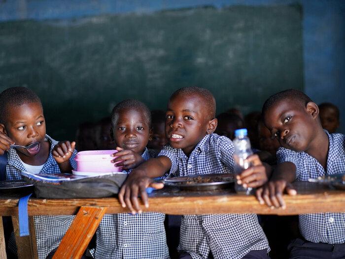 neljä lasta istuu luokkahuoneessa